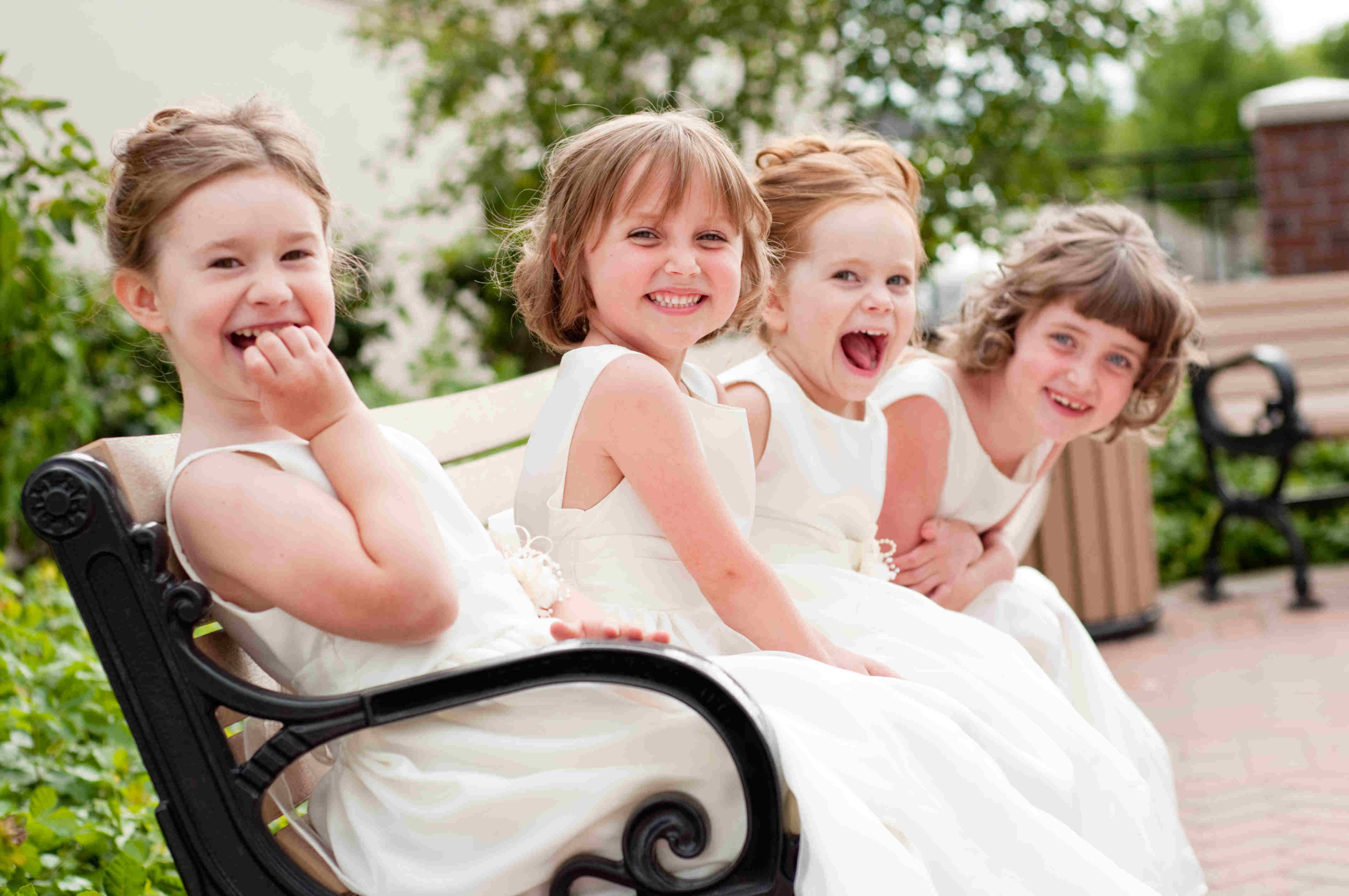 Color photo of four happy little flower girls laughing together while wearing formal dresses. They are sisters and cousins.